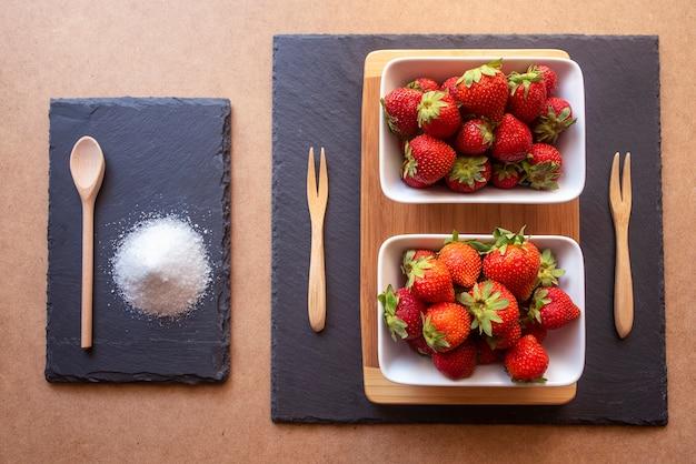 Verse en rijpe aardbeien in witte kommen