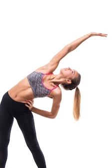 Verse energieke vrouwelijke fitness vrouw aerobics doen verschillende oefeningen die zich uitstrekken op de armen