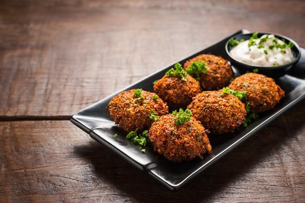 Verse falafel met peterselie en tzatziki saus in zwarte plaat op houten tafel.