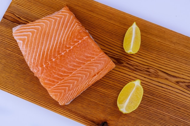 Verse filet rauwe zalm en citroen met houten snijplank op een wit
