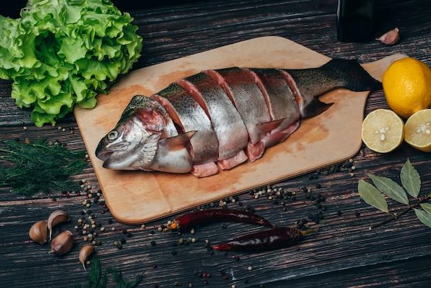 Verse forel in stukjes gesneden op een houten bord om te koken. rauwe rode vis