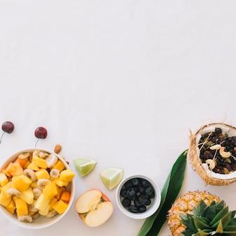 Verse fruitsalade met dryfruits in de kokosnoot die over witte achtergrond wordt geïsoleerd