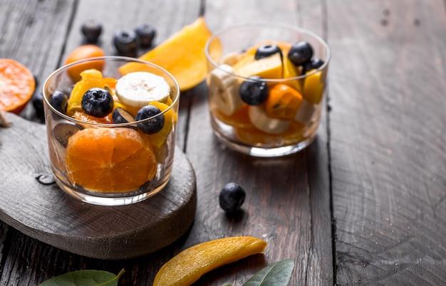 Verse fruitsalade met verschillende soorten bessen en citrusvruchten, mango geserveerd in glazen kom, geplaatst op houten tafel