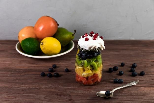 Verse fruitsalade op houten lijst