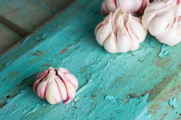 Verse garlics op turkooise houten plank