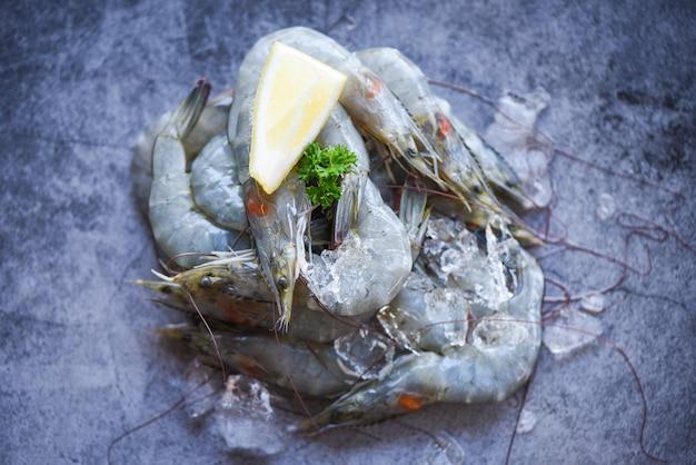Verse garnalengarnalen bij restaurant of zeevruchtenmarkt. rauwe garnalen met kruiden op donkere plaat