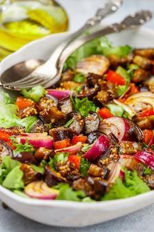 Verse gastronomische vegetarische salade van sla, gebakken aubergine, tomaten, rode uien met dressing van olijfolie