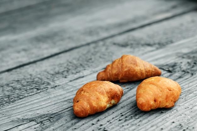 Verse gebakken croissants op houten grijs. copyspace. een goede morgen, ontbijt.