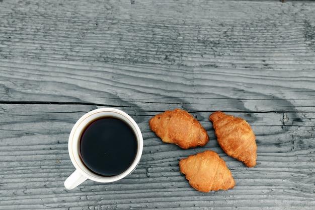 Verse gebakken croissants op houten grijs.
