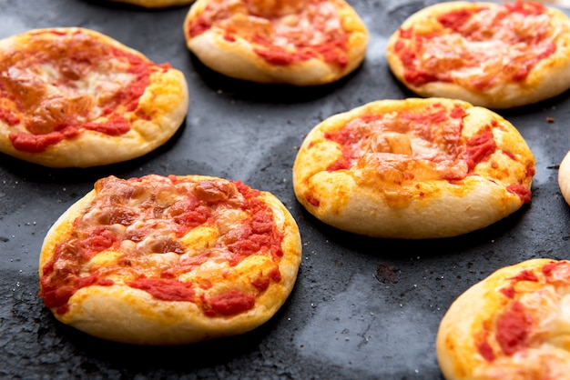 Verse gebakken kaasachtige pizzabroodjes die op pan koelen