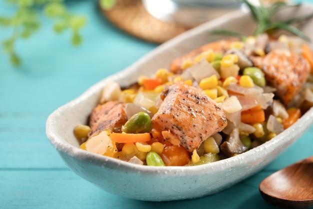 Verse gebakken zalmblokjeskoteletten met geroerbakte gemengde groenten, waaronder edamamebonen, wortel, ui, champignons en maïskorrels op blauwe houten tafel.