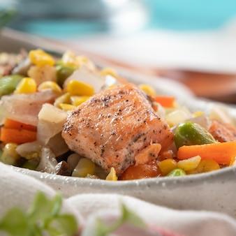 Verse gebakken zalmblokjeskoteletten met geroerbakte gemengde groenten, waaronder edamamebonen, wortel, ui, champignons en maïskorrels op blauwe houten tafelondergrond.
