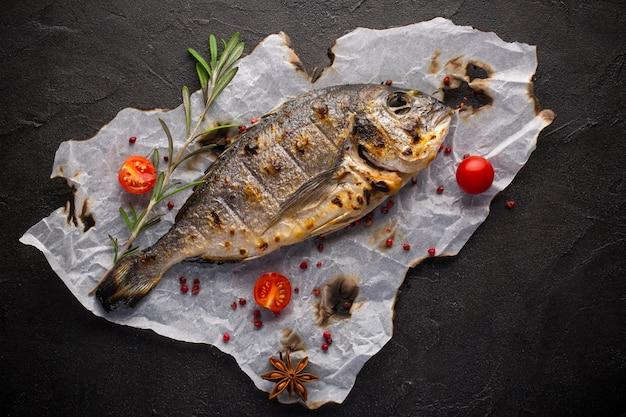 Verse gebraden dorado vissen met kruiden op zwarte achtergrond
