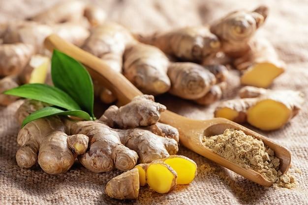 Verse gehakte gemberwortel en gemalen gemberpoeder in houten lepel op jute. gezond voedsel, kruid. zingiber officinale