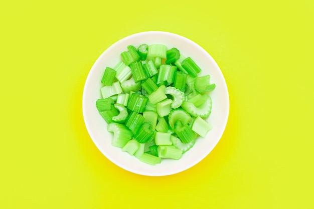 Verse gehakte selderijstukjes met waterdruppels in witte kom