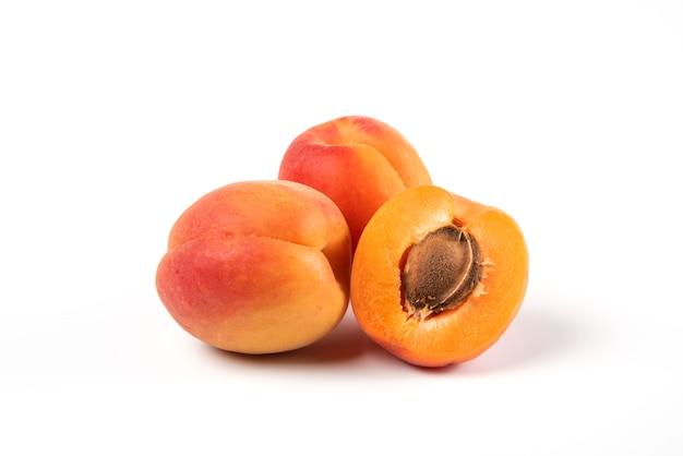 Verse gele abrikozen die op wit worden geïsoleerd