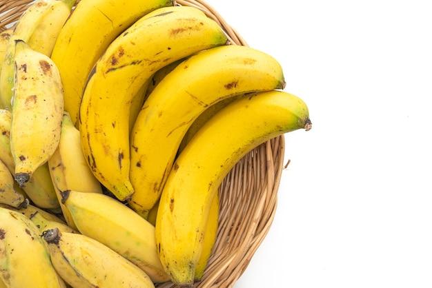 Verse gele bananen in mand die op witte achtergrond wordt geïsoleerd
