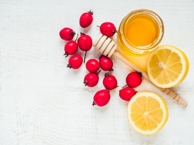 Verse gele citroen, kruik honing en rode bessen op een witte houten tafel. bovenaanzicht, close-up, geïsoleerd. concept om verkoudheid te voorkomen