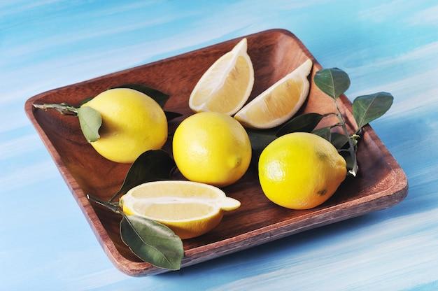 Verse gele citroenen met bladeren op een plaat op blauwe achtergrond