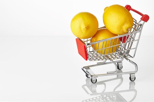 Verse gele citroenen op hakken kar geïsoleerd op witte achtergrond.