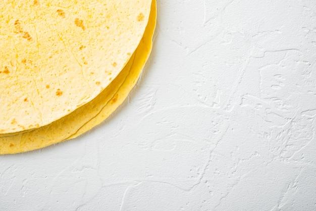 Verse gele maïstortilla's, op witte achtergrond, bovenaanzicht plat lag