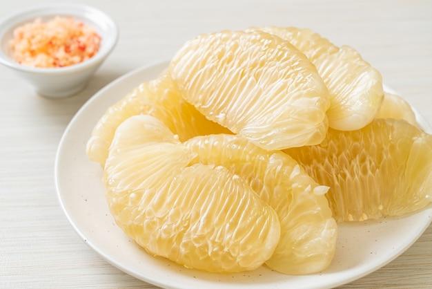 Verse gepelde grapefruit op witte plaat