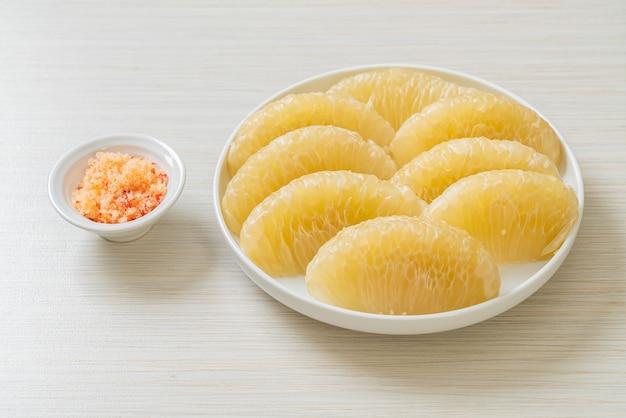 Verse gepelde pomelo, grapefruit of shaddock op witte plaat