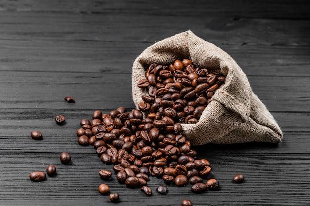 Verse geroosterde koffiebonen die de zak op de houten oppervlakte uitvallen. bruine koffiebonen verspreid uit zak op de tafel