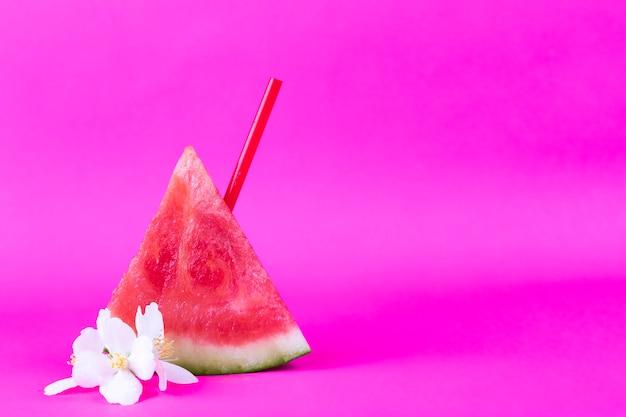 Verse gesneden watermeloen met pijp en witte exotische bloemen op een heldere roze achtergrond