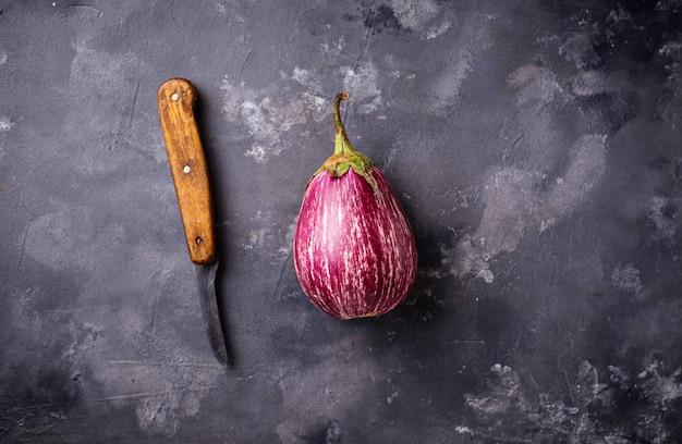 Verse gestreepte purpere aubergines op grijze achtergrond