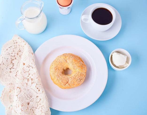 Verse gezonde bagel op een witte plaat met kopje koffie