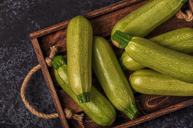 Verse gezonde groene courgette courgettes in bruine houten doos