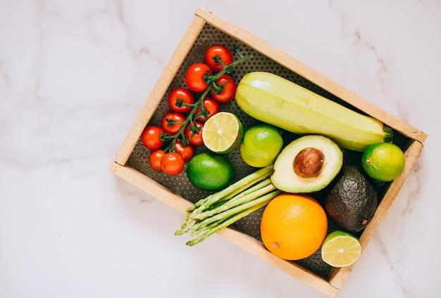 Verse gezonde groenten in houten doos op witte marmeren achtergrond