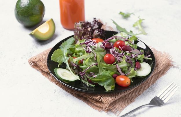 Verse gezonde groentesalade met tomaat, komkommer, spinazie, sla in plaat op tafel.