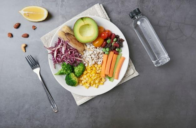 Verse gezonde groentesalade met wortel, maïs, tomaat, avocado