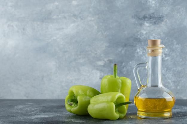Verse gezonde olie met biologische groene paprika's over grijze achtergrond.