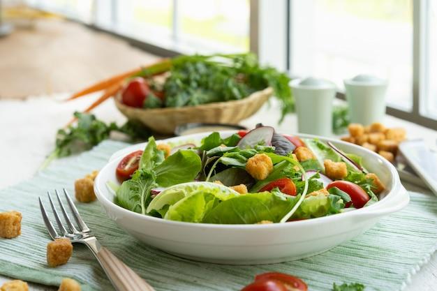 Verse gezonde plantaardige caesar salade op plaat met saus.