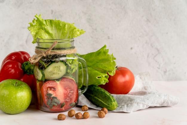 Verse gezonde plantaardige plak in metselaarkruik met vruchten en hazelnoot