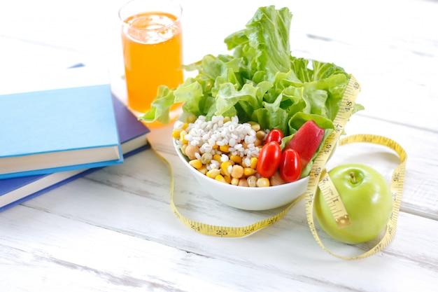 Verse gezonde salade met meetlint op de lijst.