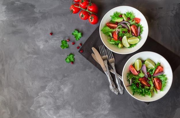 Verse gezonde salade met tomaten, avocado en granaatappel in kommen op grijs beton. kopieer ruimte gebied.