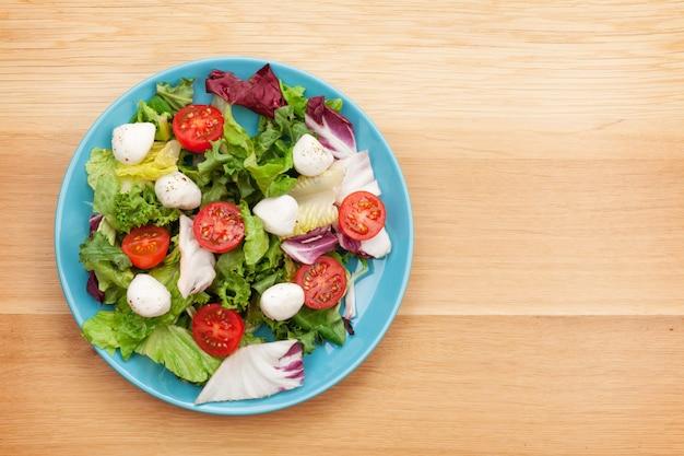 Verse gezonde salade op houten tafel met kopieerruimte