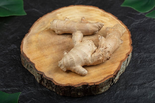 Verse gingerswortelstok of wortel op houten bord.