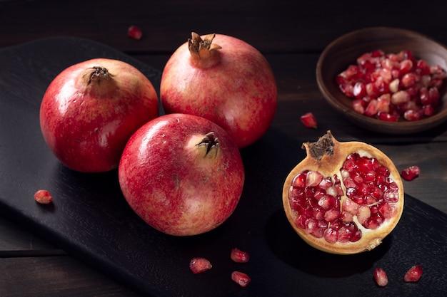 Verse granaatappels en gesneden granaatappel met zaden op houten tafel