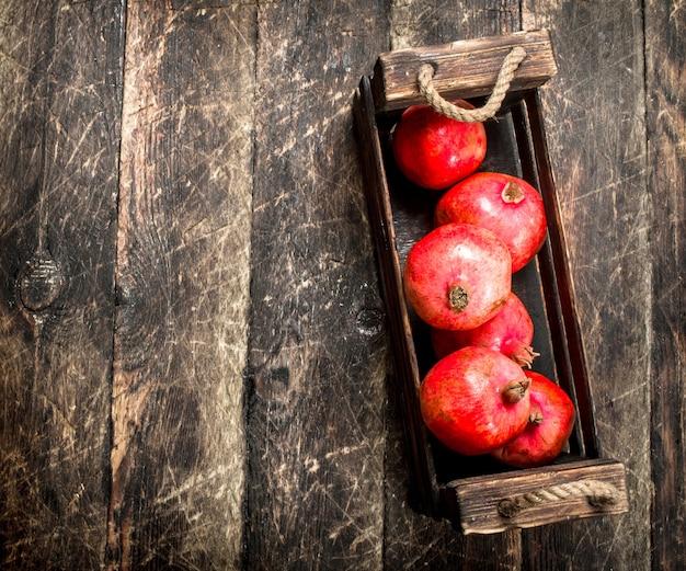 Verse granaatappels in een oude doos op een houten achtergrond