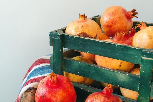 Verse granaatappels in een oude doos op houten achtergrond