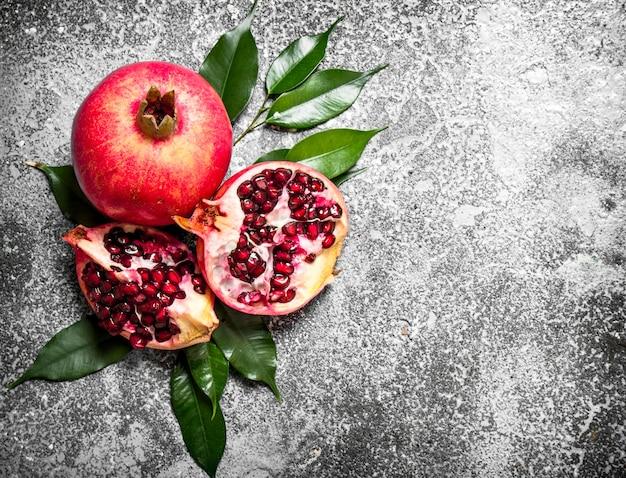 Verse granaatappels met groene bladeren op rustieke achtergrond