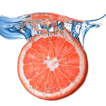 Verse grapefruit gedaald in water met bubbels geïsoleerd op wit
