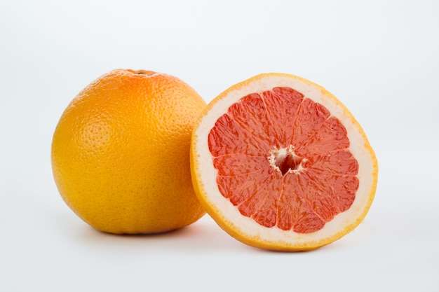 Verse grapefruit sappige rijpe zachte halve besnoeiing die op wit wordt geïsoleerd