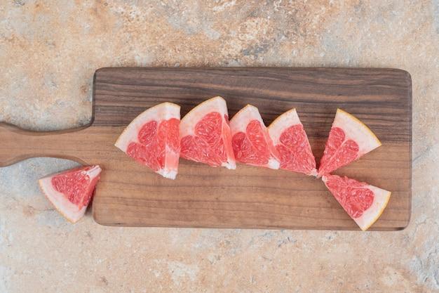 Verse grapefruitplakken op een houten bord.