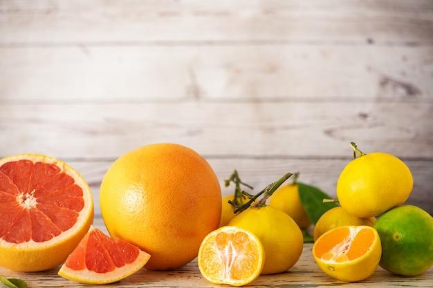 Verse grapefruits en citrusvruchten op lichte houten tafel. met kopie ruimte